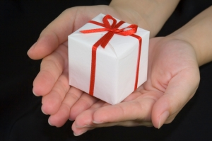 Hands holding a gift box isolated on black background